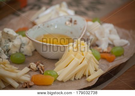 Assortment of cheese with honey and grape on a modern cutting board slate background.