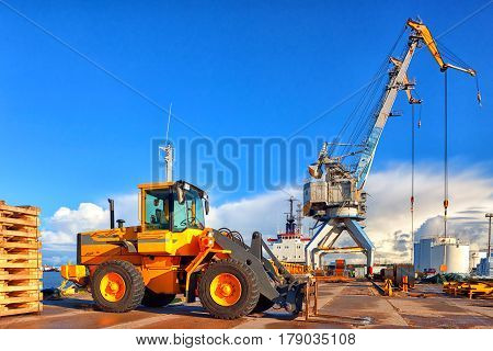 Yellow heavy truck in the background of gantry cranes around the ship on the background of the tank and the blue spring sky
