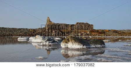 Stones with crystallized salt in old salines and ruins background, Gran canaria island