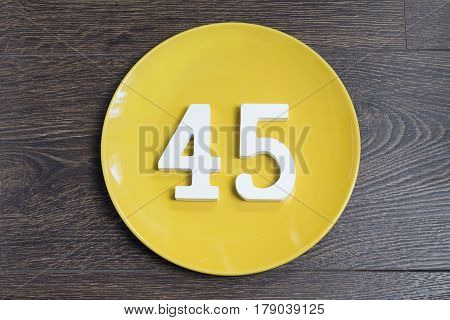 Number forty five on the yellow plate and brown background.