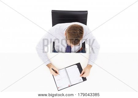 Overhead view of a handsome businessman with organizer in office. Business and office concept.