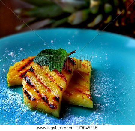 Photo of beautiful and useful dinner. Pineapple cooked on the grill and decorated with mint.