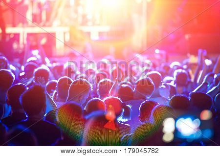 Scene and light a crowd of fans during a rock band concert
