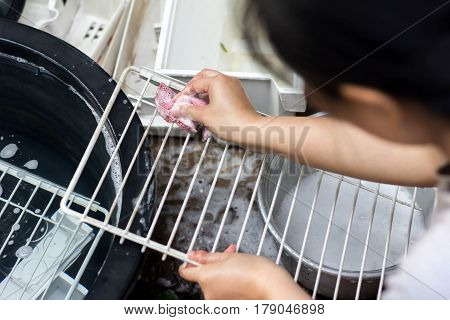 washing-up and housekeeping concept - close up of woman hands in protective gloves washing with sponge at home kitchen