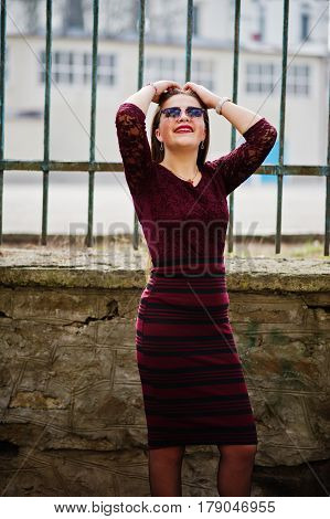 Young Chubby Teenage Girl Wear On Red Dress With Sunglasses Posed Against Iron Fence.
