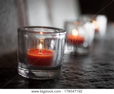 Three tealights burning and glowing in the dark