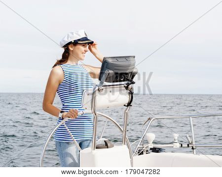 Beautiful, attractive young girl pilots a boat Mediterranean Sea. Traveling, journey, tourism, concept.