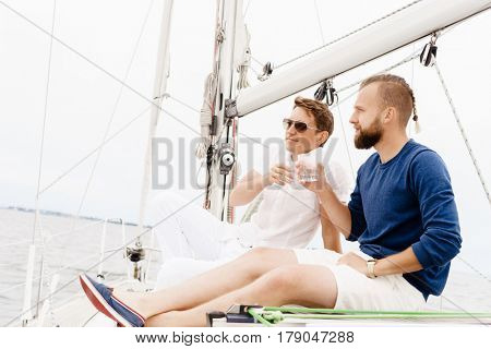Happy friends sitting together on a deck of a yacht and drinking an alcoholic drink.
