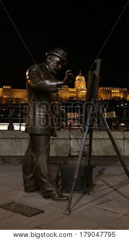 Bronze statue of Roskovics Ignac, a famous hungarian painter, with Buda castle in the background at night, Budapest