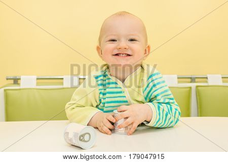 happy little baby sitting at table and smiles. beautiful child holding in his hand jar of food