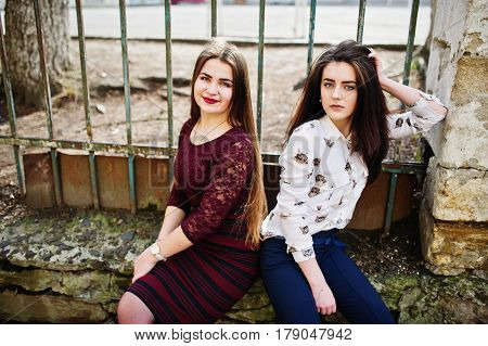Two Young Teenages Girl Sitting Against Iron Fence. Plump Girl Vs Thin. Friends Teen.