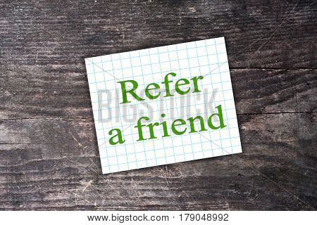 Green Refer A Friend Text On Checkered Paper Note. Dark Wooden Background