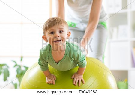 kid boy and mother doing exercises with fitness ball