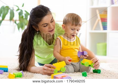 mother and kid boy play together in nursery room