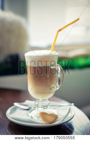 Delicious flavored coffee latte in tall glass goblet with a straw and biscuits is on the table