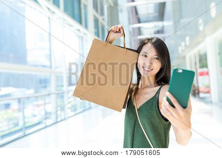 Woman holding shopping bag and taking selfie