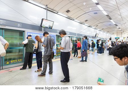 SEOUL SOUTH KOREA - MARCH 28 2017: Lots of different people standing in the line on a subway platform and waiting for their train to come - Seoul South Korea - March 28 2017