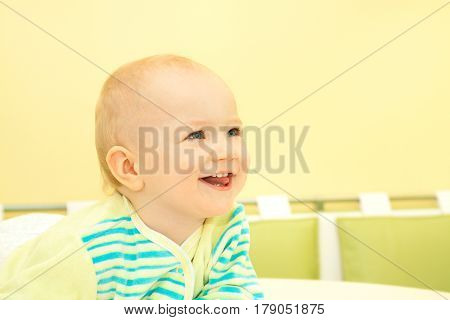 happy little baby sits at table and smiles. beautiful small child boy cheerful looking and laughs