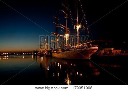 Tall Ship in the harbor at night, nicely lit, with the lights reflected in the water.