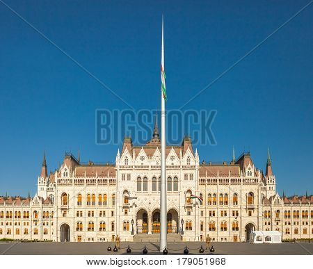 Hungarian National Parliament Building In Budapest With Huge Flagpole Near It's Left Side Entrance,