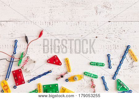 Top view on electronic constructor details and game on white wooden background. Children learning and education concept.