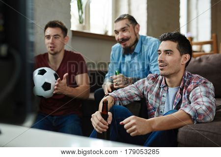 Group of friends watching football match on TV while sitting on couch and drinking beer