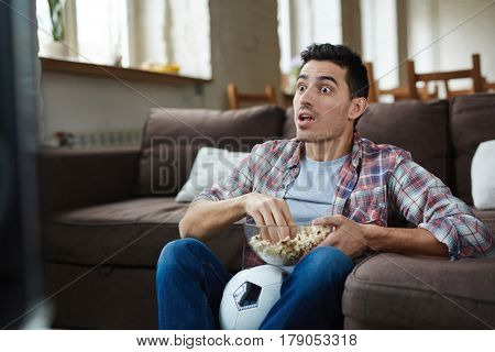 Portrait of emotional man watching football match on TV and eating popcorn looking wide eyed and shocked