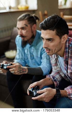 Portrait of two modern adult men, one of them heavily tattooed,  enjoying video game competition and  holding wireless controllers while sitting on couch in living room