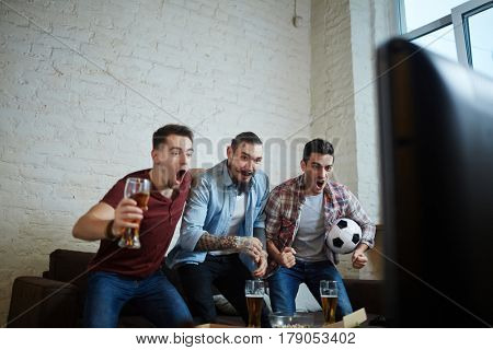 Portrait of three emotional adult men watching sport match on TV and cheering  with excitement while standing up and screaming with beer
