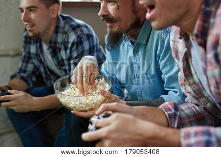 Friendly guys playing video games battle and cheering joyfully holding wireless controllers while sitting on couch in living room with popcorn