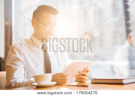 Young banker with touchpad browsing in the net at break