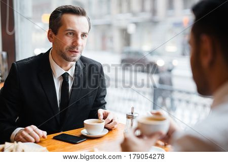 Banker speaking to one of clients or colleagues in cafe by cup of coffee
