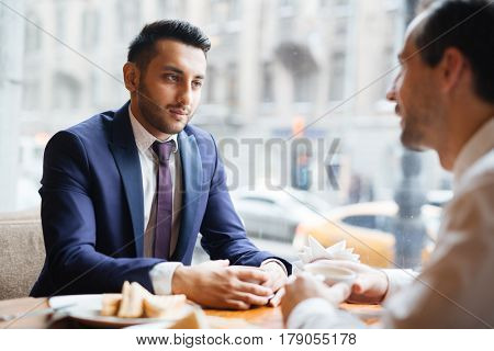 Young employee listening to colleague ideas at lunch-break
