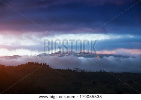 Volcano of Irazu partially hidden in clouds during sunset. Costa Rica