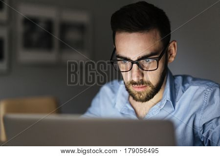 Portrait of handsome bearded man wearing glasses working with laptop in dark room late at night, his face lit up by screen