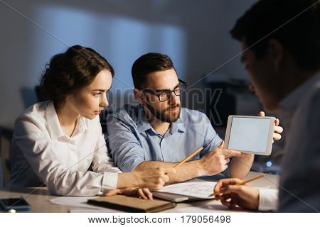 Portrait of three colleagues working overtime in dark office late at night: pointing at blank computer screen and explaining something while having lively discussion at meeting table