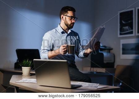 Portrait of focused bearded businessman wearing glasses working with documentation in dark room late at night, standing at workplace with heap of papers drinking coffee