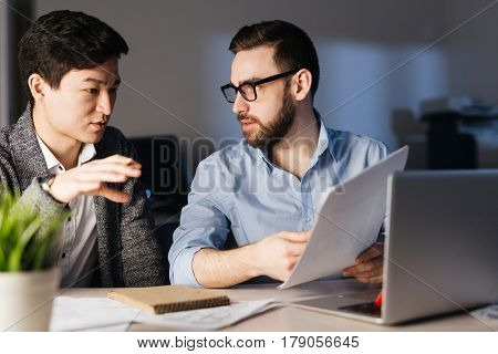 Portrait of two office workers, one of them Asian, discussing documentation in dark room late at night, faces lit by lamp light