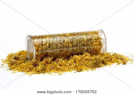 dried marigold flowers (Calendula officinalis) in a glass cylinder, on the white background