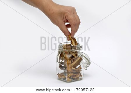 Person take slice of chopped and dried penny bun from glass jar full of mushrooms