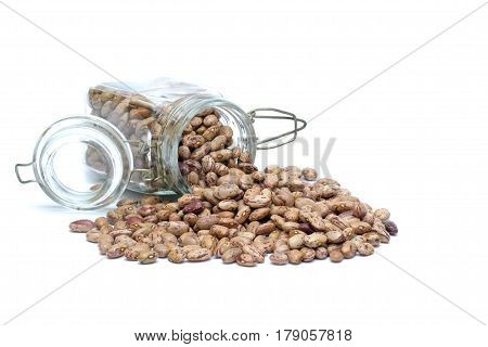 Brown beans spilled from a glass jar