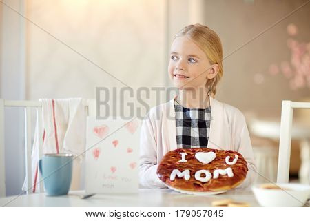 Little girl with handmade pie prepared for her mother