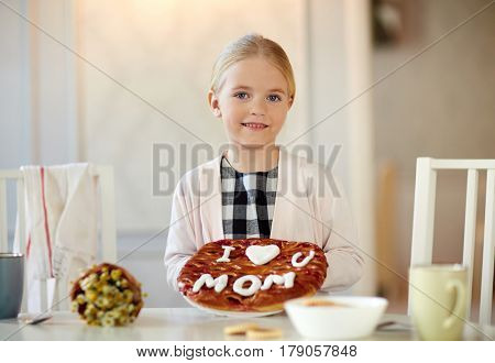 Happy girl with baked pie for mother looking at camera in the kitchen