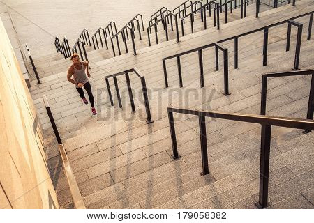 Fitness, sport, exercising and people healthy lifestyle concept - Man running upstairs in the city.