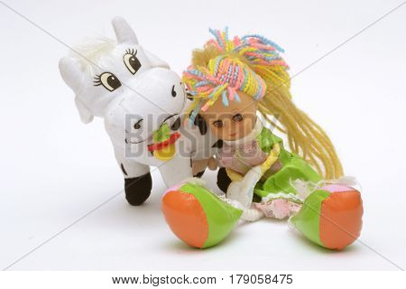 Two soft toys - doll with multicolour, wool hair sitting on a white background with a cow behind her backs