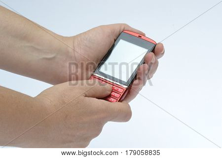 A person is typing a message on a red mobile phone