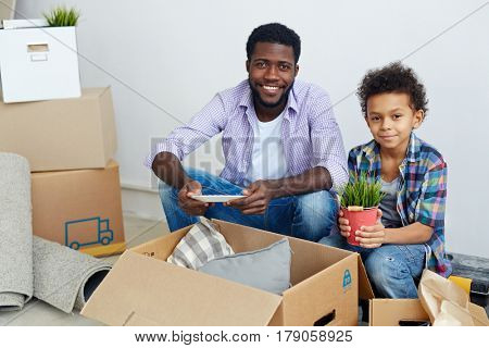 Boy holding small bucket with green plant wihile helping his father unpack boxes