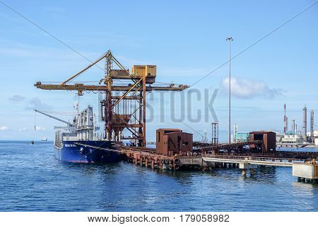 Labuan,Malaysia-Mac 25,2017:A large bulk carrier supplying iron ore in Antara Steel Mill Plant port at Labuan,Malaysia.The company produces billets and bars including angle bars and U-channels.