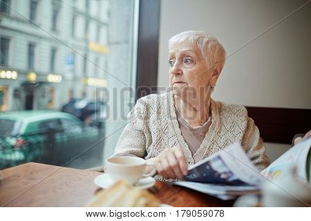 Tense woman with journal looking through window while sitting in cafe