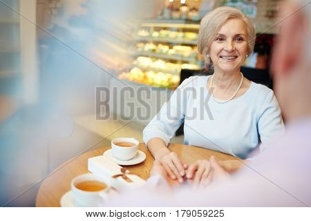 Senior spouses having romantic evening in cafe